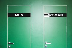 Grüne Tür zur Toilette mit dem Aufschriftmann und -frau Stockbilder