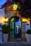 Grüne Türen verzierten warme Lichter und rosa Blumen, Grünpflanze Stockfotos