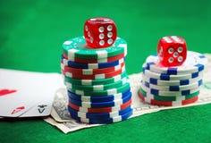 Grüne Tabelle des Kasinos mit Chips, Geld und würfelt Stockfotografie