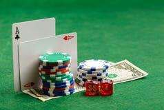 Grüne Tabelle des Kasinos mit Spielkarten, Chips, Geld und würfelt Stockfotos