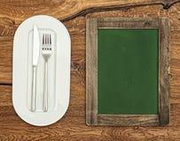 Grüne Tafel mit weißer Platte, Messer und Gabel Abbildung der roten Lilie Lizenzfreie Stockbilder