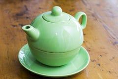 Grüne Teekanne auf einer hölzernen Kücheoberfläche Stockbild