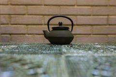 Grüne Teekanne auf grüner Tabelle und weißem Hintergrund Lizenzfreies Stockfoto