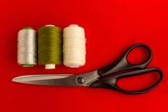 Grüne Threads, Molkereithreads und silberne Threads, Scheren mit schwarzen Griffen Stockbild