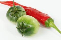Grüne Tomaten und Pfeffer der roten Paprikas Stockfotos