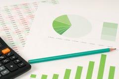 Grüne Torte und Balkendiagramme mit Taschenrechner Lizenzfreies Stockfoto