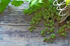 Grüne Trauben mit Blättern in einem Korb, der auf einem hölzernen Hintergrund liegt stockbilder