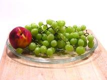 Grüne Trauben und Nektarine oder Pfirsich stockfotografie