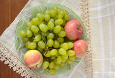 Grüne Trauben und rote Äpfel auf einer Platte Lizenzfreie Stockbilder