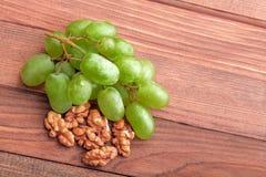 Grüne Trauben und Walnuss auf Holztisch Lizenzfreie Stockfotografie