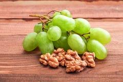 Grüne Trauben und Walnuss auf Holztisch Lizenzfreies Stockfoto