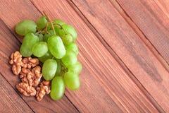 Grüne Trauben und Walnuss auf Holztisch Stockbilder