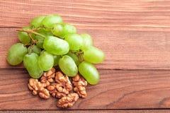 Grüne Trauben und Walnuss auf Holztisch Lizenzfreie Stockfotos