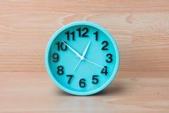 Grüne Uhr auf hölzernem Hintergrund, die Uhr, zum von Zeit zu sagen schaffen einen Winkel des Leistungshebels Stockbild