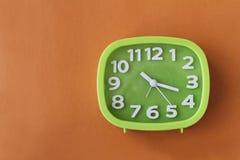 Grüne Uhr mit weißen Zahlen und Pfeile auf orange Hintergrund Stockbilder