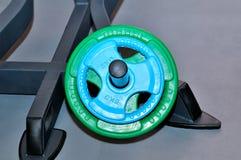 Grüne und blaue Barbellplatten auf einem Metall stehen Lizenzfreie Stockfotos