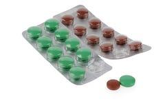 Grüne und braune Pillen in den Blasen Stockfotografie