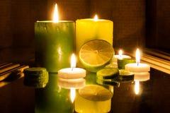 Grüne und gelbe brennende Kerzen des Badekurort-Konzeptes, Scheibe der Zitrone Stockbild