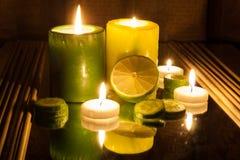 Grüne und gelbe brennende Kerzen des Badekurort-Konzeptes, Scheibe der Zitrone Stockbilder