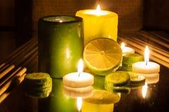 Grüne und gelbe brennende Kerzen des Badekurort-Konzeptes, Scheibe der Zitrone Lizenzfreie Stockfotografie