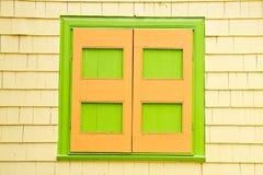Grüne und orange Blendenverschlüsse auf gelbem Abstellgleis-Haus Lizenzfreie Stockfotografie