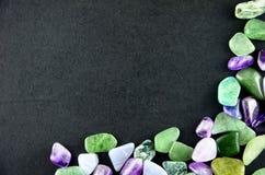 Grüne und purpurrote Steine auf schwarzem Hintergrund Lizenzfreie Stockfotografie