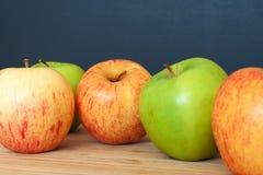 Grüne und rosa Äpfel auf einem hölzernen und schwarzen Hintergrund Stockbild
