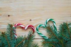 Grüne und rote Herzen von Süßigkeitskegeln mit Weihnachtsbaumasten auf dem hölzernen Hintergrund Neues Jahr oder Valentinsgrußtag Stockfoto