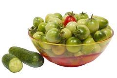 Grüne und rote Tomaten und Gurken in der Schüssel Lizenzfreie Stockfotografie