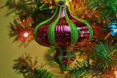 Grüne und rote Weihnachtskugelnahaufnahme auf einem Weihnachtsbaum Stockfotografie
