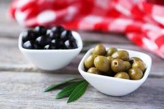 Grüne und schwarze Oliven in der Schüssel auf grauem hölzernem Hintergrund Lizenzfreies Stockbild