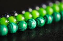 Grüne und schwarze Perlen von einem Stein Lizenzfreie Stockfotos