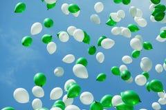 Grüne und weiße Ballone im Himmel Stockfotos