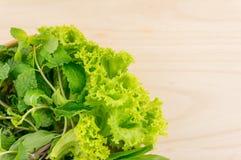 Grüne vegatables in der hölzernen Platte auf hölzernem Hintergrund Stockfoto