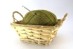Grüne Verwicklung der natürlichen Wolle für Näharbeit mit einer gewirkten Häkelarbeit fest in ihr in einem Weidenkorb auf einem w Lizenzfreies Stockfoto