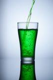 Grüne Wasserströme in das Glas und macht Blasen Stockfoto