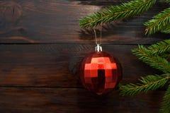 Grüne Weihnachtsbaumaste auf einem dunklen hölzernen Hintergrund Hintergrund des neuen Jahres mit einer roten Glaskugel Beschneid Stockfotografie