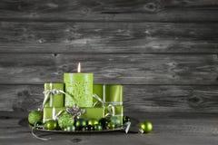 Grüne Weihnachtsdekoration mit Kerze und Geschenken auf hölzernem GR Lizenzfreies Stockfoto