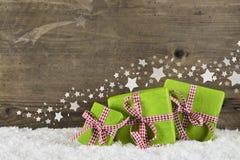 Grüne Weihnachtsgeschenke auf hölzernem Hintergrund für ein Geschenk certifi lizenzfreies stockbild