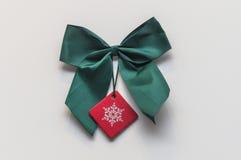 Grüne Weihnachtsschleife mit rotem Aufkleber und weißem Hintergrund Stockfotografie