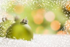 Grüne Weihnachtsverzierungen auf Schnee über einem abstrakten Hintergrund Stockbilder
