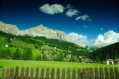 Grüne Wiese im alpinen Dorf, Dolomit, Italien Stockbild