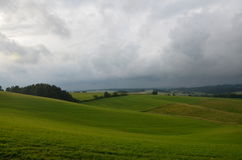 Grüne Wiese mit drastischem Himmel Stockfotografie