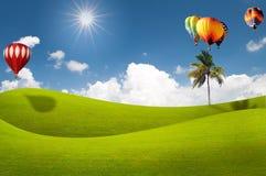 Grüne Wiese mit Heißluftballon über blauem Himmel Lizenzfreies Stockfoto