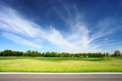 Grüne Wiese und blauer Himmel mit Asphaltstraße Stockfotografie