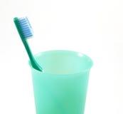 Grüne Zahnbürste und Teller lizenzfreies stockfoto