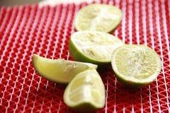 Grüne Zitrone auf rotem Hintergrund Lizenzfreie Stockbilder