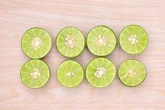 Grüne Zitrone geschnitten auf einen Holztisch Stockbilder