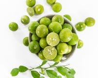 Grüne Zitronen mit Blatt in der Schüssel Lizenzfreies Stockfoto