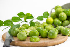 Grüne Zitronen mit Hackklotz Stockfotos